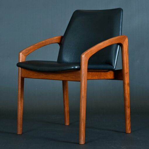 Classic Danish teak armchairs by Kai Kristiansen. The vintage mid-century modern chairs are covered in black vinyl fabric.